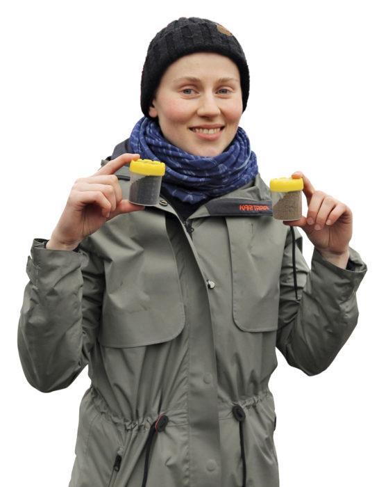 Caroline Karlsson Ruotsin maatalousyliopistosta pitelee käsissään kahta pientä purkkia, joiden avulla taika tapahtuu. Toisessa on tuhkaa ja toisessa biohiiltä. Niiden avulla virtsa muuntuu jauhomaiseen, kasveille käyttökelpoiseen muotoon.