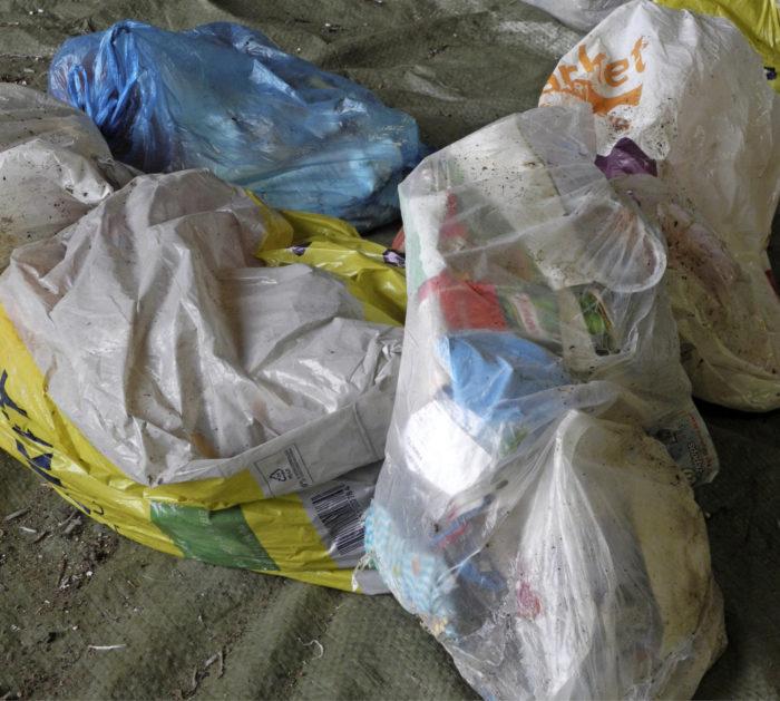 Roskapussit on kumottu jäteastiasta pressulle odottamaan avaamistaan.