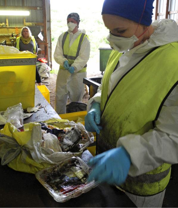 Hengityssuojaimia tarvitaan. Mötkähtäneet liha- ja marinadijäämät haisevat. Taustalla työtä seuraa Outi Ruuska.