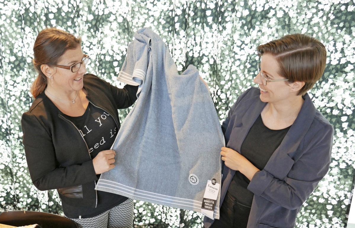 Henna Knuutila (vas.) ja Elli Ojala esittelevät kierrätetystä kuidusta valmistettua Finlaysonin pyyheliinaa.
